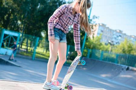 Skater female rides on skateboard at skate park ramp. Young woman practising skateboarding outdoors at skate park.