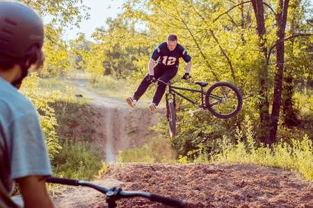 acrobacias geniales realizadas por un ciclista-atleta profesional. En un campo de deportes del bosque, con saltos de esquí, saltando al cielo. Andar en bicicleta en el bosque. Ciclismo. Joven milenario en un casco realiza saltos