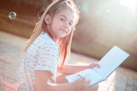 teenage girl sitting on a skateboard, writing on a notebook, smiling, looking at the camera. Against the background of the setting sun. In warm colors