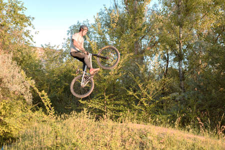 cool stunts performed by a professional cyclist-athlete. In a forest sports field, with ski jumps, jumping into the sky. Biking in the forest. Cycling. Young millennial in a helmet performs jumping
