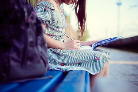 Portrait of a beautiful teenage girl with a backpack. Sitting on a bench writing in a notebook. Outdoor