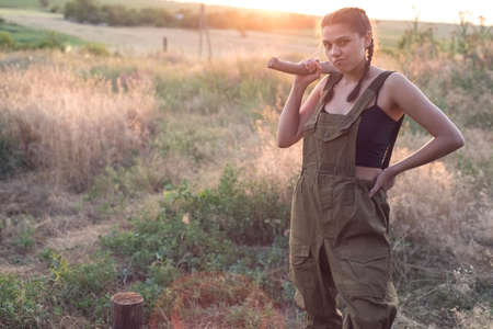 portrait of a beautiful young model girl. In working equipment, a woman works with an ax, waves, stands in a field. Country style