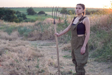 Portrait of a beautiful young farmer girl. Stands with a pitchfork in the field. Women doing hard man work