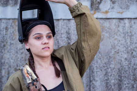 portrait of a beautiful girl, in uniform, with a welding helmet, and a big key in her hands. The concept of women doing hard, masculine work