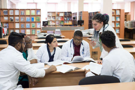 young doctors, mixed race. They sit at the table, solve medical problems. People of different sexes, in white coats, medical clothes, are sitting at a table in the office of the hospital