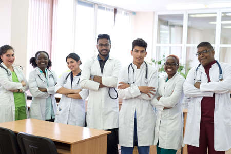 medical students, doctors, mixed race. A team of young people in white coats posing in the hallway of the hospital