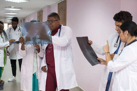 medical students, interns. Young doctors, mixed race, in the corridor of the hospital, consultation. X-ray images of patients are examined, medical problems are solved