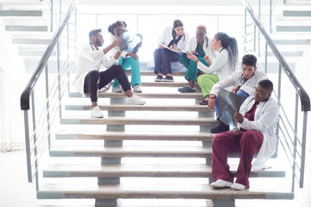 young doctors, mixed race, sitting, standing on the steps, in the corridor of the hospital. They consider x-rays, use gadgets to work in medicine. People in medical clothes.
