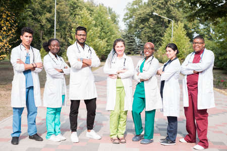 team of young doctors, mixed race. Posing in the photo, for advertising. People in white coats, with phonendoscopes, outdoors