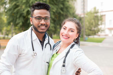 Indian young doctor with glasses, handsome. Hugs a white woman doctor. Young men in white coats hugging, outdoor Stock Photo