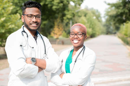 portrait of young doctors. Indian guy, black girl. People in white coats, glasses, with stethoscopes. Outdoor in