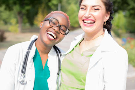 Portrait of smiling doctors, mixed race. Black girl, white girl, laughing, happy. People in white coats with stethoscopes. Outdoor in