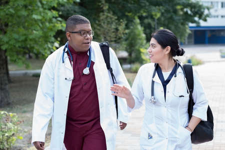 Portrait of walking young interns. Young people, in surgical suits, white coats, with backpacks, with stethoscopes, mixed race. Black guy and mexican girl