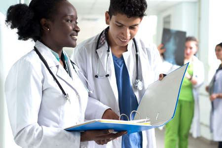 portrait of doctors, mixed race. A black girl, with a Mexican guy, in white coats, with stethoscopes, is holding medical documents, a consultation, a conference in her hands. In the background, doctors examining x-rays of patients