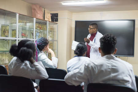 doctors, mixed race, in the classroom, at a medical conference. Young people, in white coats, with stethoscopes, are studying medicine. Classroom, anatomical museum. Students raise their hand to answer the question of the teacher, professor
