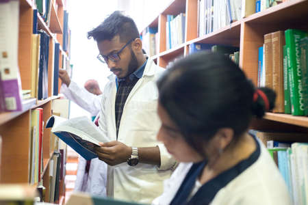 medical university students in a library looking for medical literature. Young people in white coats, mixed race.