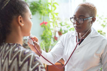 A black girl doctor examines a Mexican patient in a doctors office carries out auscultation of the lungs with a stethoscope