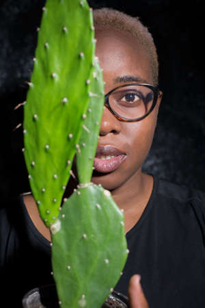 portrait of an african girl in glasses. Half of the face is covered by a cactus. On a dark background. Dramatic light