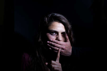Victim of domestic violence, Human trafficking concept, End to violence against women,Scared woman with man's hand covering her mouth Archivio Fotografico