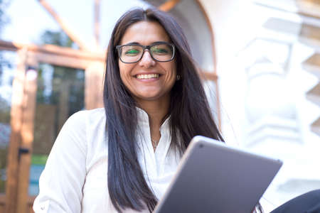 portrait of a beautiful indian girl in glasses. Business woman in a strict shirt, smiling, uses a tablet, notepad. Sitting on a bench, on the street, on the steps. Talking on the phone, conducts a business conversation.