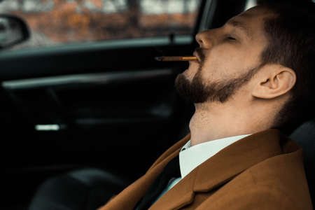 Portrait of a young drunk guy sleeping with a cigarette while driving a car. Close-up. In a warm, creative tone. Danger of falling asleep while driving a car with a cigarette. Fire hazard smoking cigarettes while driving