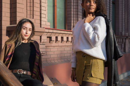 A pair of beautiful young fashionable Spanish girls, against the background of a brick office building. Posing for the camera. Generation Z. beautiful girls, young fashion models. Advertising photo. Fashionable photo. Mixed race of young people. Street art Reklamní fotografie