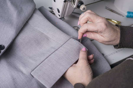 a couturier master, against the background of a sewing machine, sews clothes from high-quality fabric, the manual work of a professional clothing manufacturer. The process of manufacturing a jacket, b