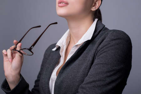 Portrait of a young beautiful business woman, in a business suit, holds glasses for vision in her hand, dreaming. On a gray background. Women in business, lady in a jacket. Matriarchy. Sexy lips of an office girl