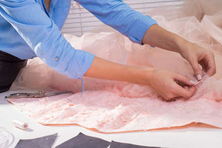 couturier designer, in his clothing manufacturing studio. Handmade clothing, professional sews decorative flowers on a pink dress. The process of making clothes, sewing, measuring fabric, clothing tailoring.