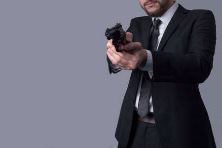 Portrait of a bearded man in a business suit holds an aiming revolver. On a gray background. Criminal type man, gangster, killer, businessman killer