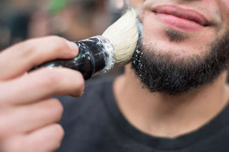 Closeup of a barber putting some shaving cream on a clients face before giving him a shave shaving a beard to a caucasian man. Lathers a beard, preparing it for a haircut. Barber Shop Professional Beard Care Stock fotó
