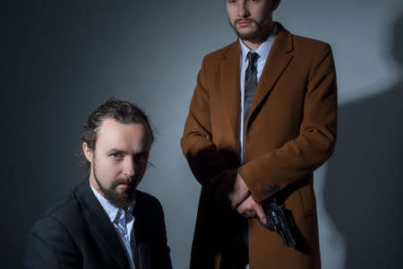 Portrait of two men in business suits, one of them is sitting, the other is holding a gun. On a gray background. Dramatic light. Artistic setting. The concept of criminal authorities. Businessmen bandits. Disassembly businessmen Stock fotó