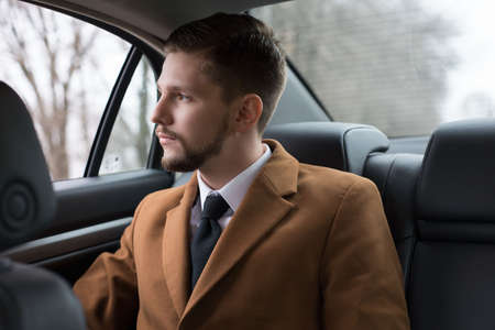 portrait of a young guy with a beard. A businessman in a car in the passenger seat rides to the office, to work. Businessman 30 years old. in a suit and a white shirt with a tie. Business style. Businessman man rides in a car Standard-Bild