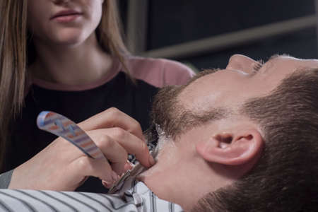 Close up process of haircut and beard care. A professional master prepares a clients beard for cutting and shaving a beard. The beauty of men. Barbers, beard and temples care salad.