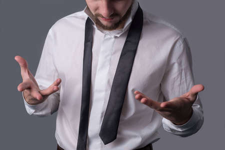 A portrait of a young bearded man in a white shirt indignantly shrugs, pointing to a tie, amid the inability to tie a tie correctly. On a dark gray background. Business dress code, a man is going to an important meeting. Demonstration of masculinity, elegance and business image.
