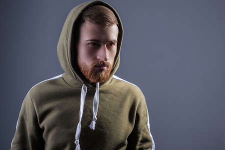 Studio portrait of a young bearded guy of twenty-five years old. in a sports jacket with a swamp-colored hood. On a gray background. Advertising photo of a handsome guy. in a sports warm jacket with a hood. green military color. In wireless headphones Reklamní fotografie