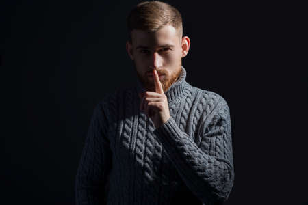 studio portrait of a young bearded guy of twenty-five years old. In a warm winter sweater, proudly, gray, looking at the camera and holding a finger to his mouth, with the background for a call to silence. On a black background. in a dramatic artistic light. Crazy Discount Promotional Photo Reklamní fotografie