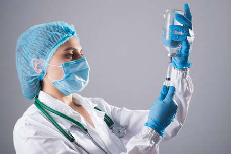 Portrait of a doctor, close-up. in a protective suit against infections, sterile conditions. picks up a syringe medicine from a glass vial. On a gray background. Female doctor. in a mask and hat, gloves and a white coat with a phonendoscope, gaining a solution of sodium chloride from a bottle. with a syringe