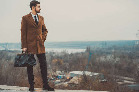 Portrait of a young guy of thirty years old, in a business style, with a leather bag in his hands. Against the sky, street style. Business concept. In creative tinting Reklamní fotografie