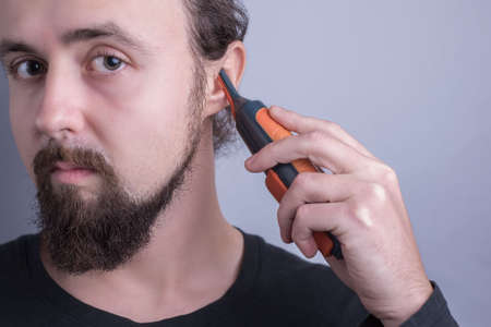 Portrait of a young bearded guy using a trimmer to cut hair in his ears. On a gray background. ear care in men. Excessive hair growth on the ears. A guy looking at the camera cuts his own hair in the ears with a clipper