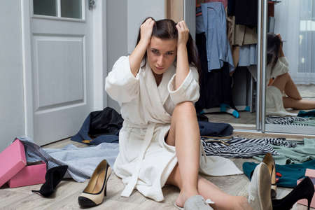 portrait of a beautiful young girl in a home white coat, sitting on the floor in the room with scattered things, looking at the wardrobe, thoughtfully choosing what to wear. Concept of how girls are going for a long time