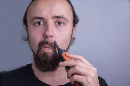 Close-up portrait of a young guy using a mustache trimmer. Beard and mustache care. A man trimmed his mustache with a trimmer, looking at the camera. Stock fotó