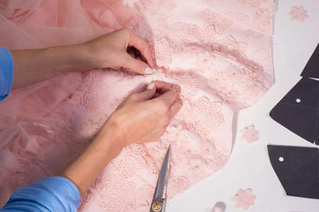 Top view of a couturier designers workplace in his clothing manufacturing studio. Handmade clothing, professionally sews decorative flowers on a pink dress. The process of making clothes, sewing, measuring fabric, sewing clothes.