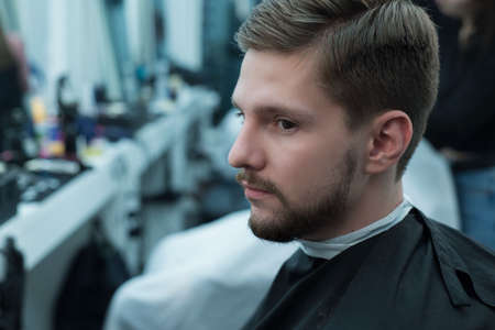 Close-up. Master hairdresser does hair styling so that the bearded guy combed his hair with a comb. Musk style and beauty. Barbershom. The hairdresser. Care for mens hair. Mens beauty Reklamní fotografie