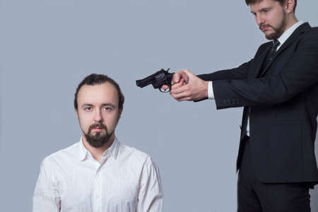 business man in a suit aiming a gun at the head of another man in a white shirt. on a gray background. The concept of killing. Business killing. Criminal showdown between businessmen. Murder for the purpose of profit. Men shoot another man