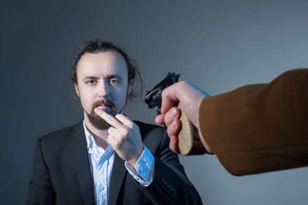 closeup portrait of a man showing his middle finger, whose face is pointing his hand with another mans gun. On a gray background. The concept of killing. Dramatic picture. The business of disassembling criminal authority. Close range killing. Point blank shot from a pistol
