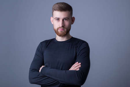 studio photo of a young bearded guy, an athlete posing on a gray background for a sports magazine, in a running long-sleeve t-shirt. Skinny sportswear