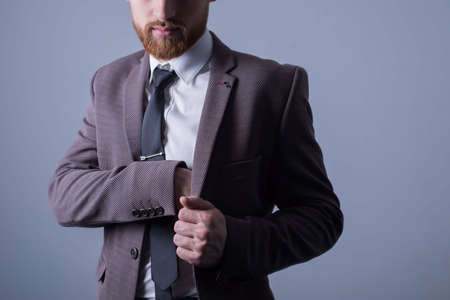 Studio portrait of a young bearded handsome guy of twenty-five years old, in an official suit, sticks his hand in the inside pocket of his jacket. on a gray background.