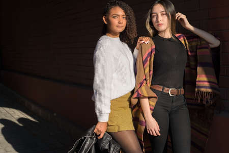 Portrait of two beautiful fashionable Hispanic girls, happy smiling posing for the camera. Autumn street art photo. Background to the autumn sale. fashion photography. Models are posing. Mixed race of young people. Generation Y, Z