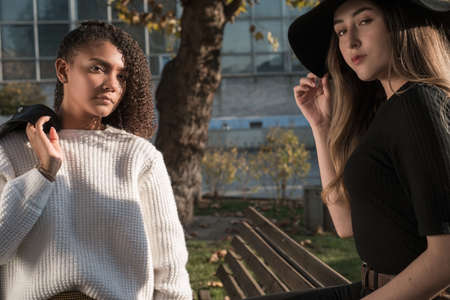 pair of young beautiful mexican generation girls. The girl is sitting on the back of the bench in a black hat, a girlfriend is standing next to curly hair and a white sweater, holding a jacket on her shoulder Zdjęcie Seryjne